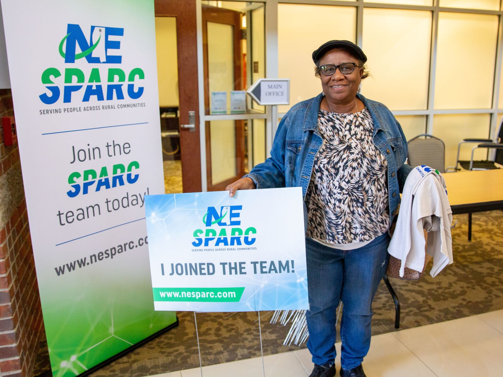African American woman standing next to signage. NE SPARC. Serving people across rural communities. Join the SPARC team today. www.nesparc.com. NE SPARC. Serving people across rural communities. I joined the team! www.nesparc.com.
