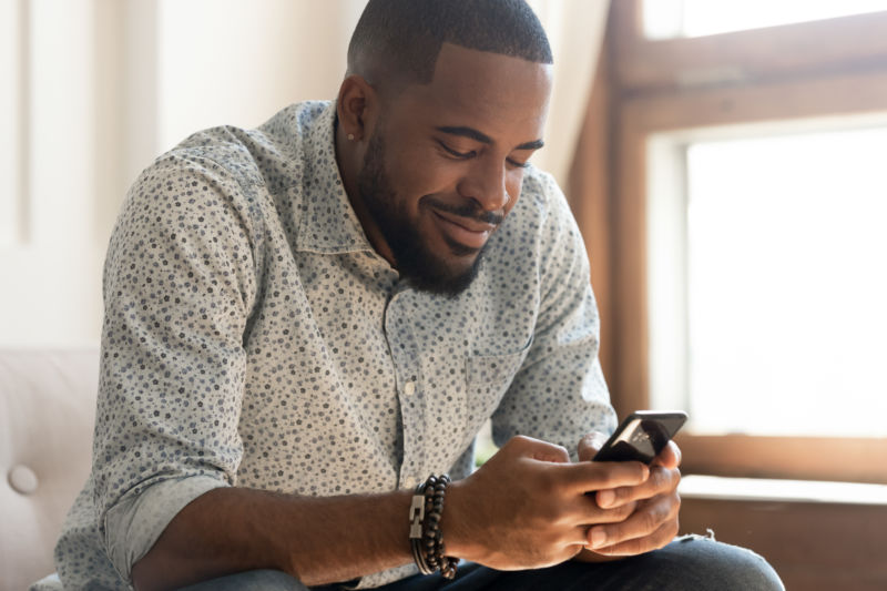 African American man sitting down while looking at cell phone