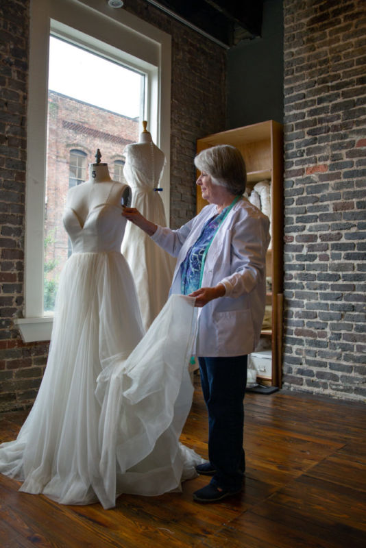 Combs works on fitting a gown to a dress form at Heidi Elnora Atelier in Birmingham.