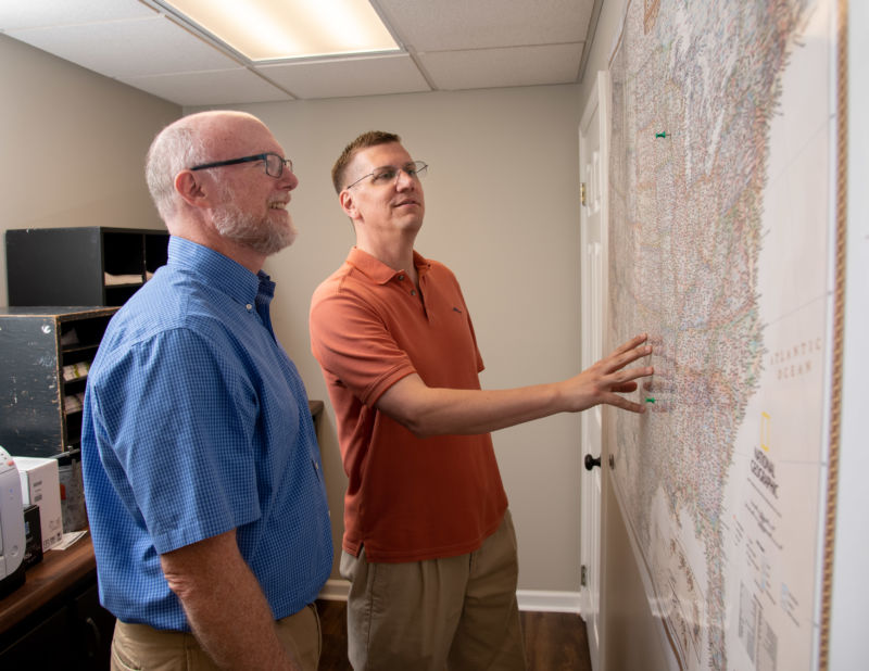 Two employees examining a map of the United States