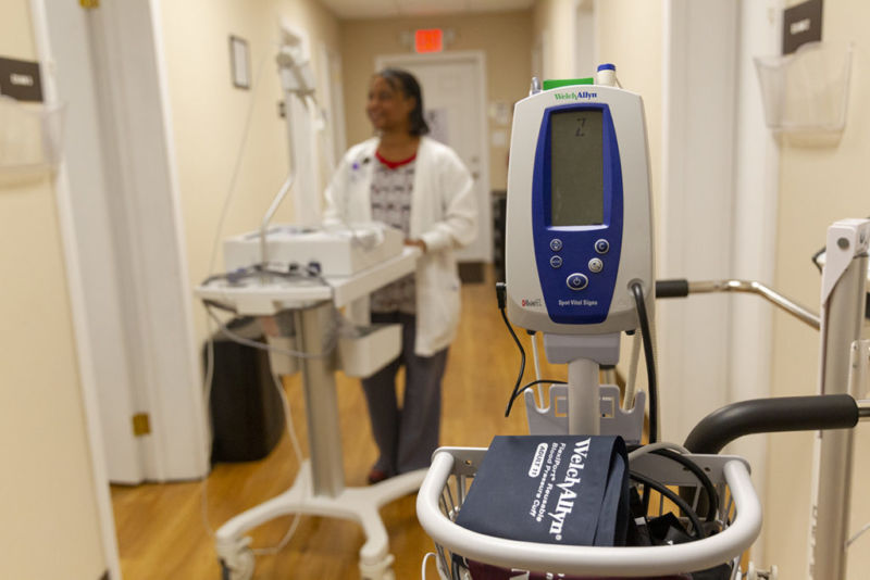 Jolanda Burr, RN, transports the electrocardiogram machine down the hallway in the clinic.