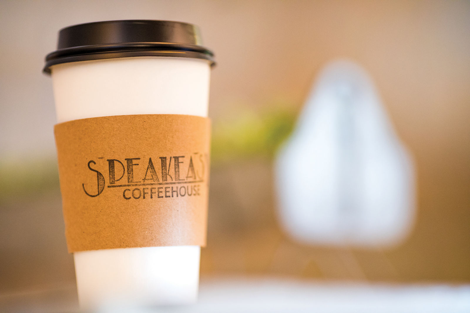 disposable coffee cup with Speakeasy Coffeehouse logo